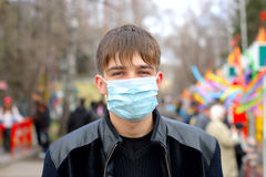 Teenager in mask. Teenager in the flu mask on the street Royalty Free Stock Images