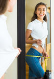 Teenager measuring waist by centimeter Royalty Free Stock Images