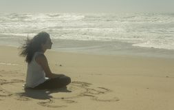 Teenager meditating on the beach royalty free stock images