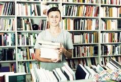 Teenager mit Buchstapel im Shop Stockfotos