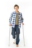 Teenager mit Krücken und einem Verband auf seinem rechten Bein Stockbild