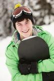 Teenager mit Snowboard am Ski-Feiertag stockbild