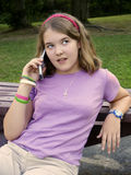 Teenager with mobile phone. Teenager with mobile telephone on bench in countryside royalty free stock photography