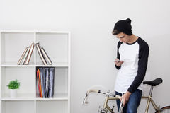 Teenager with the mobile phone. On bicycle vintage white background Stock Photo