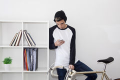 Teenager with the mobile phone. On bicycle vintage white background Royalty Free Stock Photos