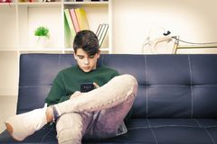 Teenager with mobile phone. On the sofa at home Royalty Free Stock Photo