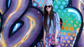 Teenage girl on the street. Teenager model with long hair wearing sunglasses and hat posing against a background of multi-colored wall, smiling stock video footage
