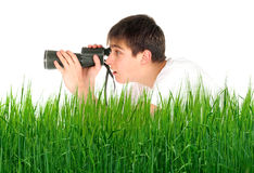 Teenager with monocle. Amazed teenager is spying for someone in the grass Royalty Free Stock Photos