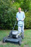 Teenager Mowing the Lawn 2. Red-haired teenaged young man mowing the lawn on a bright summer day stock images