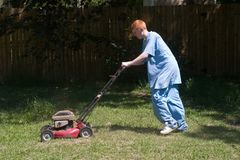 Teenager Mowing the Lawn 6. Red-haired teenaged young man mowing the lawn on a bright summer day royalty free stock images