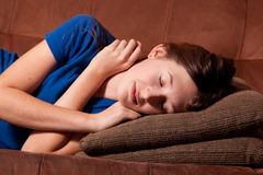 Teenager napping on couch Royalty Free Stock Photos