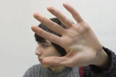 Teenager nascondendo il suo fronte. Immagine Stock