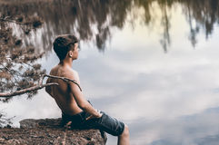 Teenager near the lake sits on a rock Stock Photos