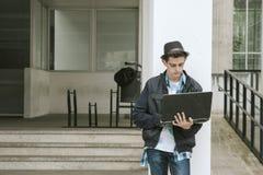 Teenager nell'università con il computer portatile Fotografia Stock