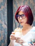 Teenager nerd asiatico avendo scossa di cioccolato immagine stock
