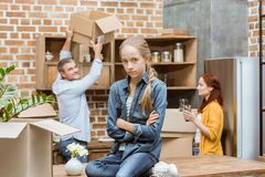 Teenager at new home. Upset teenager with arms crossed looking at camera with parents behind at new home Stock Photo
