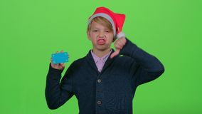 Teenager in the new year hat with a credit card shows dislike on a green screen stock video footage