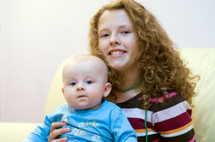 Teenager with newborn brother Stock Photo