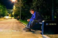 Teenager in the night. Lonely teenager sitting in the night park alone Royalty Free Stock Photos