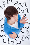 Teenager with no clue. Teenager has no clue - standing on question marks with a lost expression Stock Photos