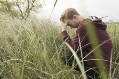 Teenager in open field praying Stock Photo