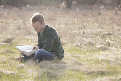 Teenager in open field reading Bible Stock Photography