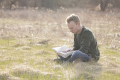Teenager in open field reading Bible Stock Image