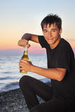 Teenager opens beer bottler on stone seacoast Royalty Free Stock Photos