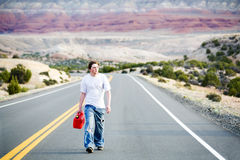 Teenager out of gas. Walking down rural mountain road with gas can royalty free stock photo