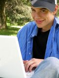 Teenager outside happy with a laptop closeup. Teenager is outside busy enjoying his laptop, closeup picture stock photography