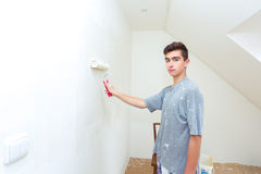 Teenager painting wall to white at home Stock Images