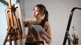 A teenager paints a painting with paints on canvas, which stands on an easel. An adult teenager holds in his hand a palette with oil paints, a canvas on which a stock video footage