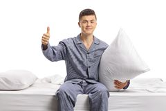 Teenager in pajamas seated on a bed holding a pillow and making. A thumb up gesture isolated on white background Royalty Free Stock Image