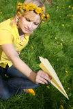 Teenager and paper plane. Teenager sitting on a glade of dandelions and throwing a paper plane Stock Photography