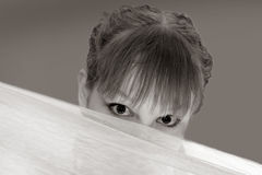 Teenager peering over object Royalty Free Stock Photography