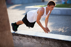 Teenager performing push-ups outdoor in city Royalty Free Stock Photography