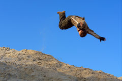 Teenager performs gliding jump on sand hill royalty free stock image