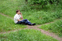 Teenager on phone in forest crossroad choose path  Stock Photo