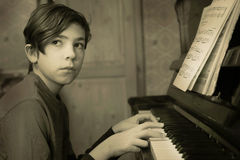 Teenager pianist boy playing piano with music notes Royalty Free Stock Image