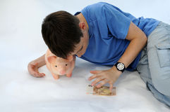 Teenager with piggy bank Stock Images