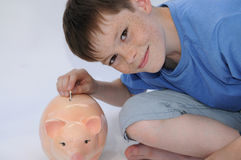 Teenager with piggy bank. Teenager boy puts a banknote in  his piggy bank Royalty Free Stock Image