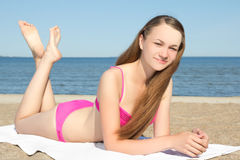 Teenager in pink bikini lying on the beach Royalty Free Stock Photography