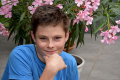 Teenager and pink oleander. Cute teenager boy sitting in front of a pink oleander Stock Photography