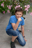 Teenager and pink oleander. Cute teenager boy sitting in front of a pink oleander Royalty Free Stock Images