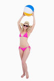 Teenager in a pink swimsuit raising a beach ball Stock Image