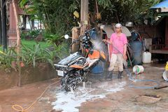 Teenager in a pink t-shirt, cap and rubber boots washes a scooter. Motor scooter in white royalty free stock image