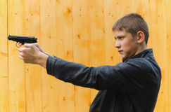 Teenager with a pistol Stock Photo