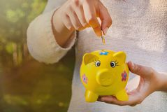 Teenage girl places coin into piggy bank to save for the future. Teenager places coin into piggy bank to save for the future Royalty Free Stock Photo