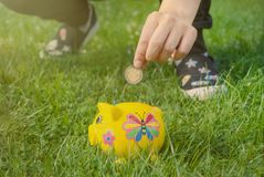 Teenage girl places coin into piggy bank to save for the future. Teenager places coin into piggy bank to save for the future Stock Images