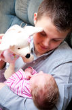 Teenager playing with baby. Teenage boy playing with baby sister on sofa or settee Royalty Free Stock Photography
